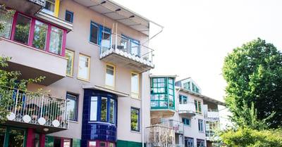 På bilden syns en bostadsrättsförenings fasad. Fasaden har många balkonger i olika färger och former.
