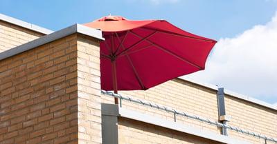 På bilden syns en husfasad med ett rött parasoll på en balkong. Fasaden är i gult tegel.