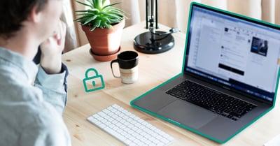 På bilden syns en person i förgrunden som sitter framför en laptop och funderar på begreppet IT-säkerhet.
