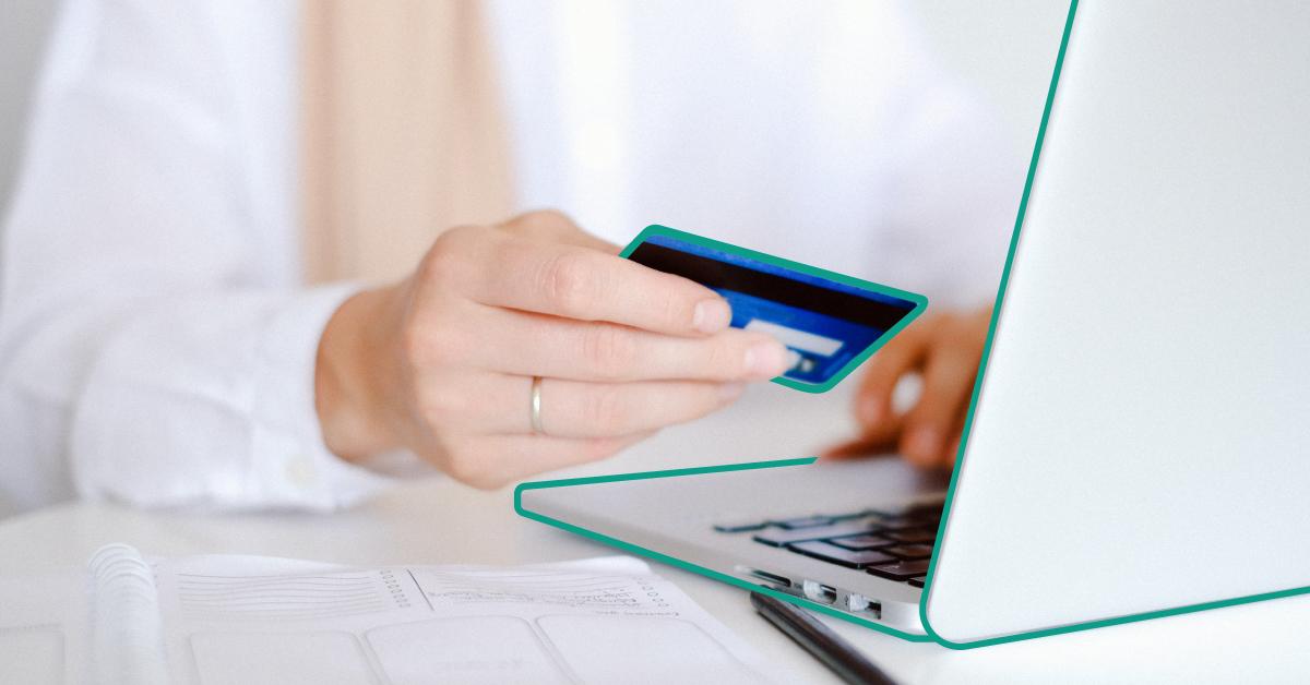 Person i vit skjorta håller upp sitt blå betalkort framför sin laptop.