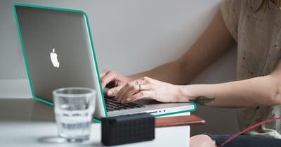 Fotografi på en persons händer som skriver på en laptop. På bordet står det ett glas vatten och en laptop.