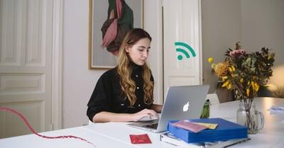 Fotografi på en tjej som sitter och arbetar hemifrån framför sin laptop.