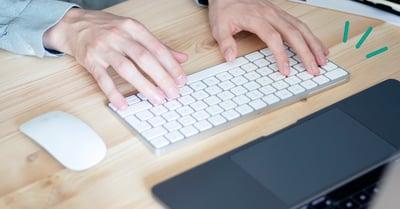 På bilden syns två ljusa händer som knappar på ett tangentbord. Tangentbordet ligger på ett ljust skrivbord i furu.