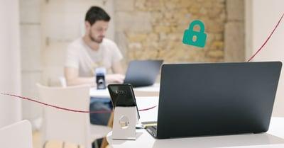 Bild på en man som sitter och jobbar vid sin dator på ett kontor. Hänglåset i hörnet indikerar om IT-säkerhet.