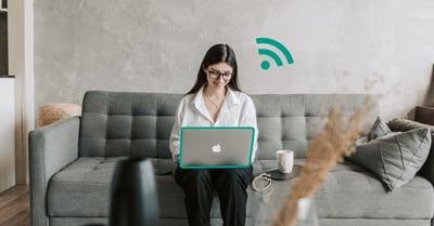 Fotografi på en kvinna som sitter i en soffa med en laptop i knäet. Hon har en illustrerad WiFi-symbol ovanför datorn som indikerar att hon har WiFi 6.