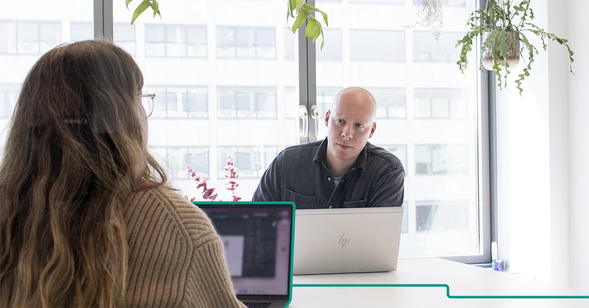 En man i svart skjorta sitter framför sin laptop och ser bekymrad ut, mitt emot honom sitter en kvinna i en brun stickad tröja framför sin laptop. Bakom mannen syns en företagsbyggnad.